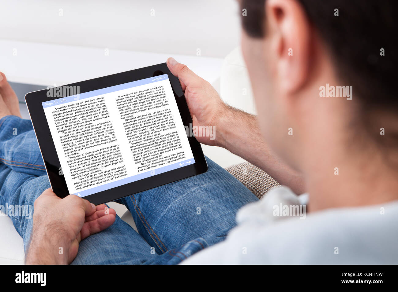 Close-up Of Man Holding Touch Screen Device Showing An E-book - Stock Image