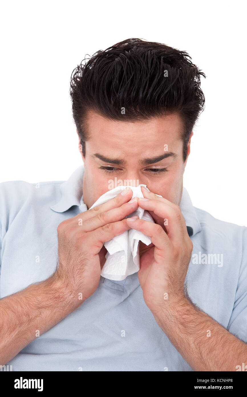 Young Man Blowing His Nose In A Tissue Over White Background - Stock Image
