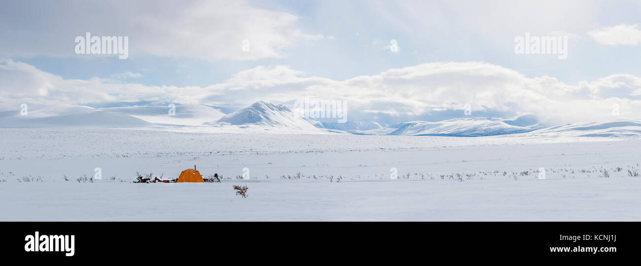 Snowmobilers camp under the McKenzie Mountains overlooking a high tundra plateau in the middle of winter's grip - Stock Image