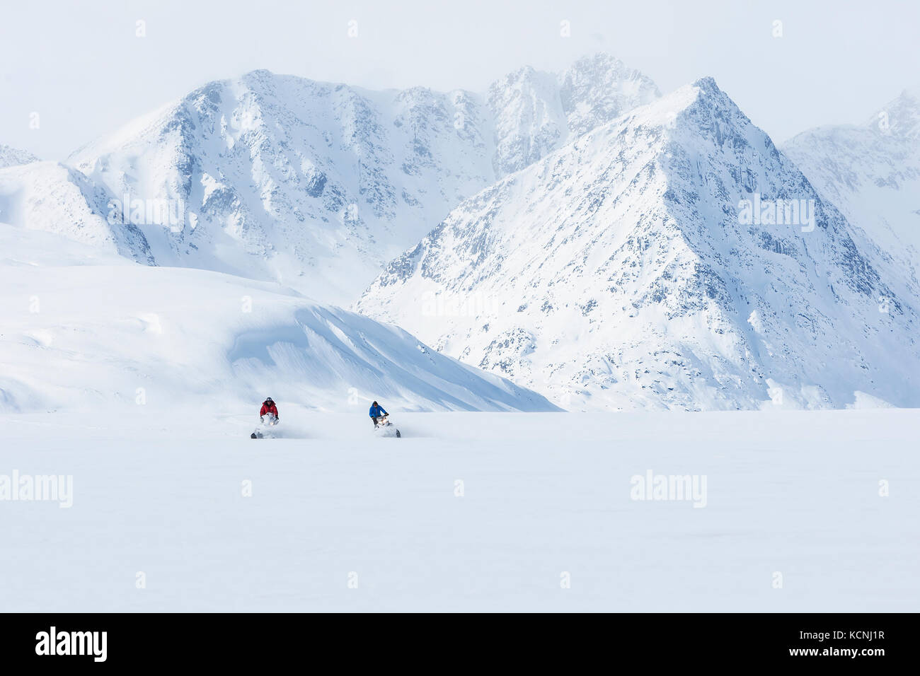 Two snowmobilers carve through soft dry powder on the North Canol Trail near MacMillan Pass, Yukon Territory, Canada - Stock Image