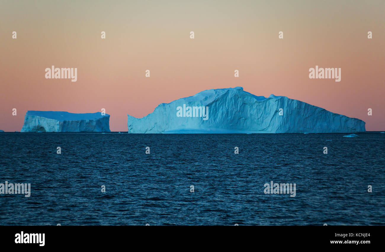 Twilight finds Icebergs floating in water against an orange cloudless sky near Fournier Bay, Antarctic Peninsula Stock Photo