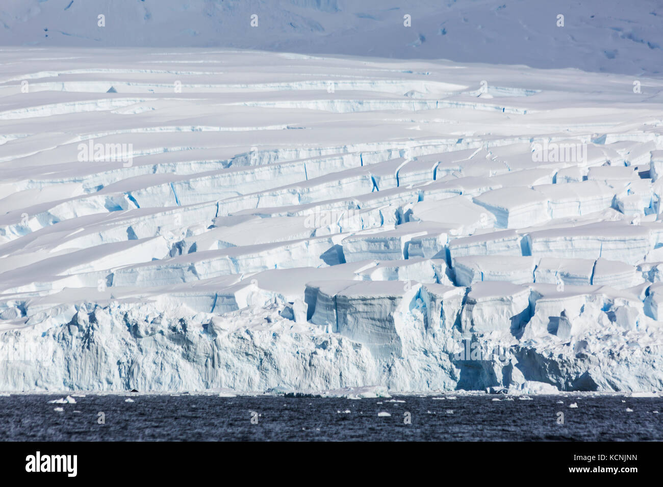 Heavily glaciated ice reaches out to waiting water in Wilhelmina Bay, Gerlache Strait, Antarctic Peninsula - Stock Image