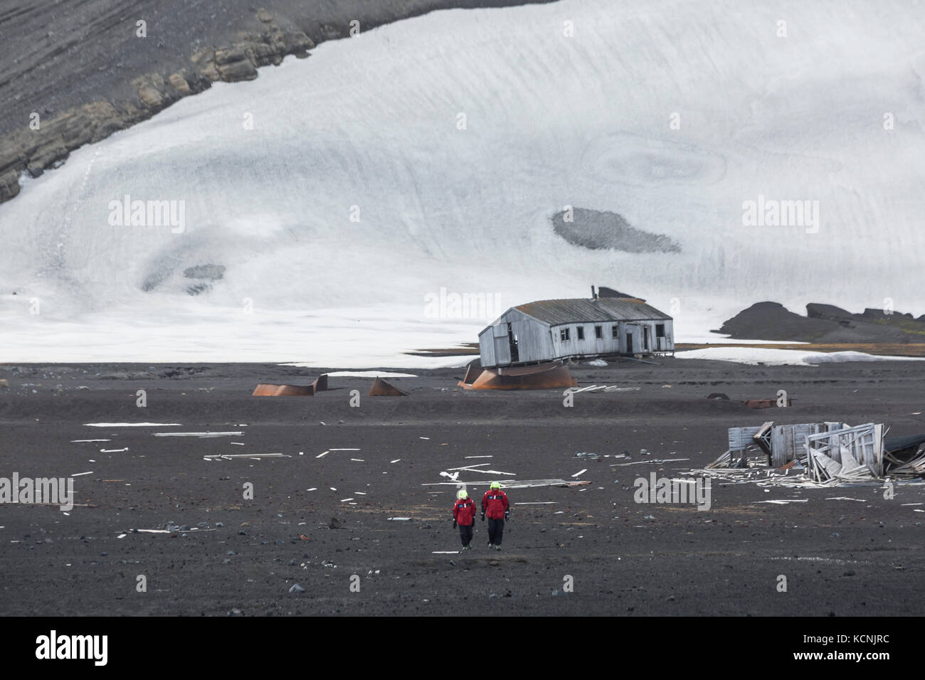 Two adventure tourists walk along the volcanic landscape and deteriating buildings of Deception Island,  South Shetland - Stock Image