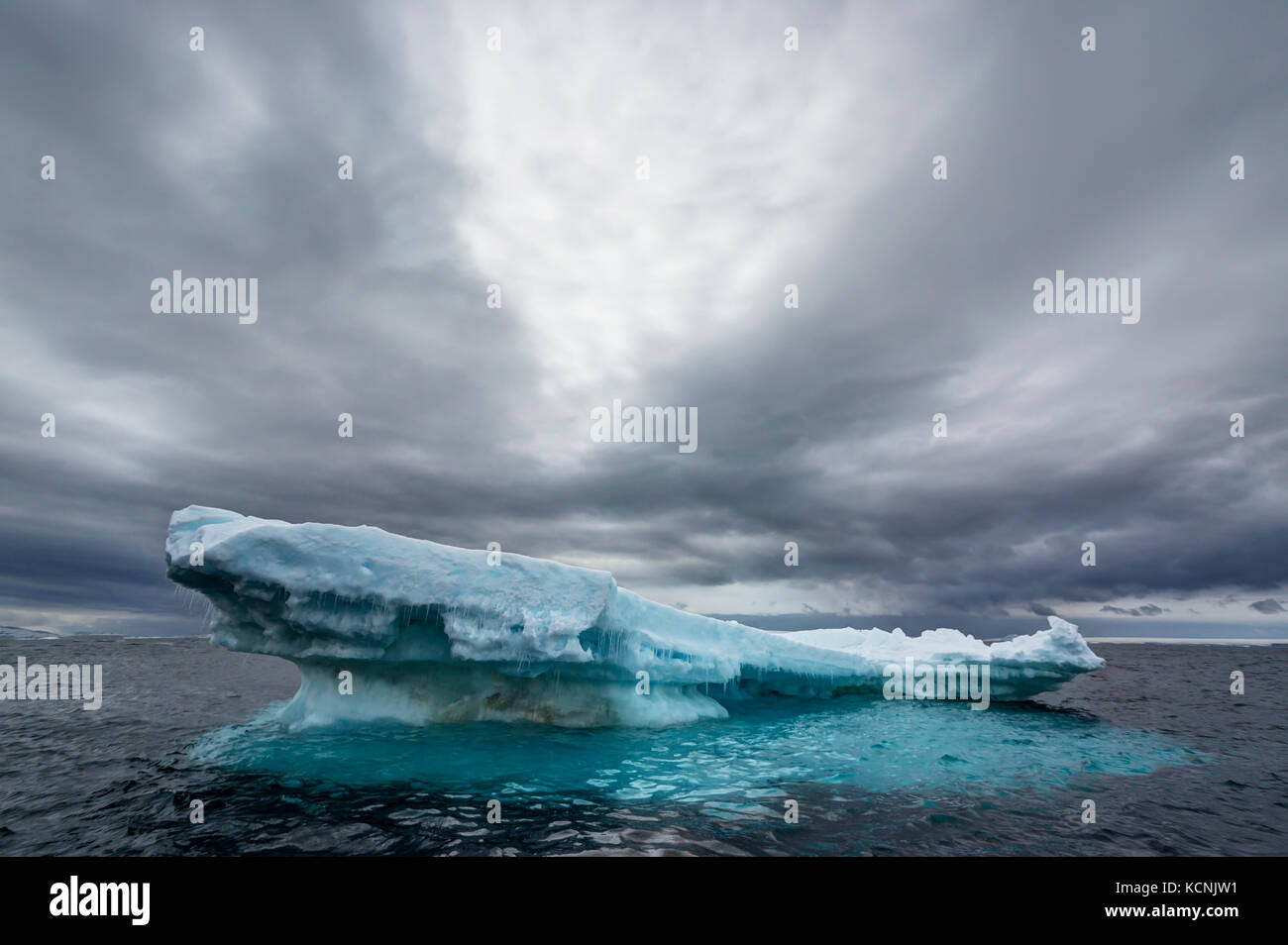 An floating iceberg slowly gives way to the Ocean's inevitable onslaught under a dramatic sky near Joinville - Stock Image