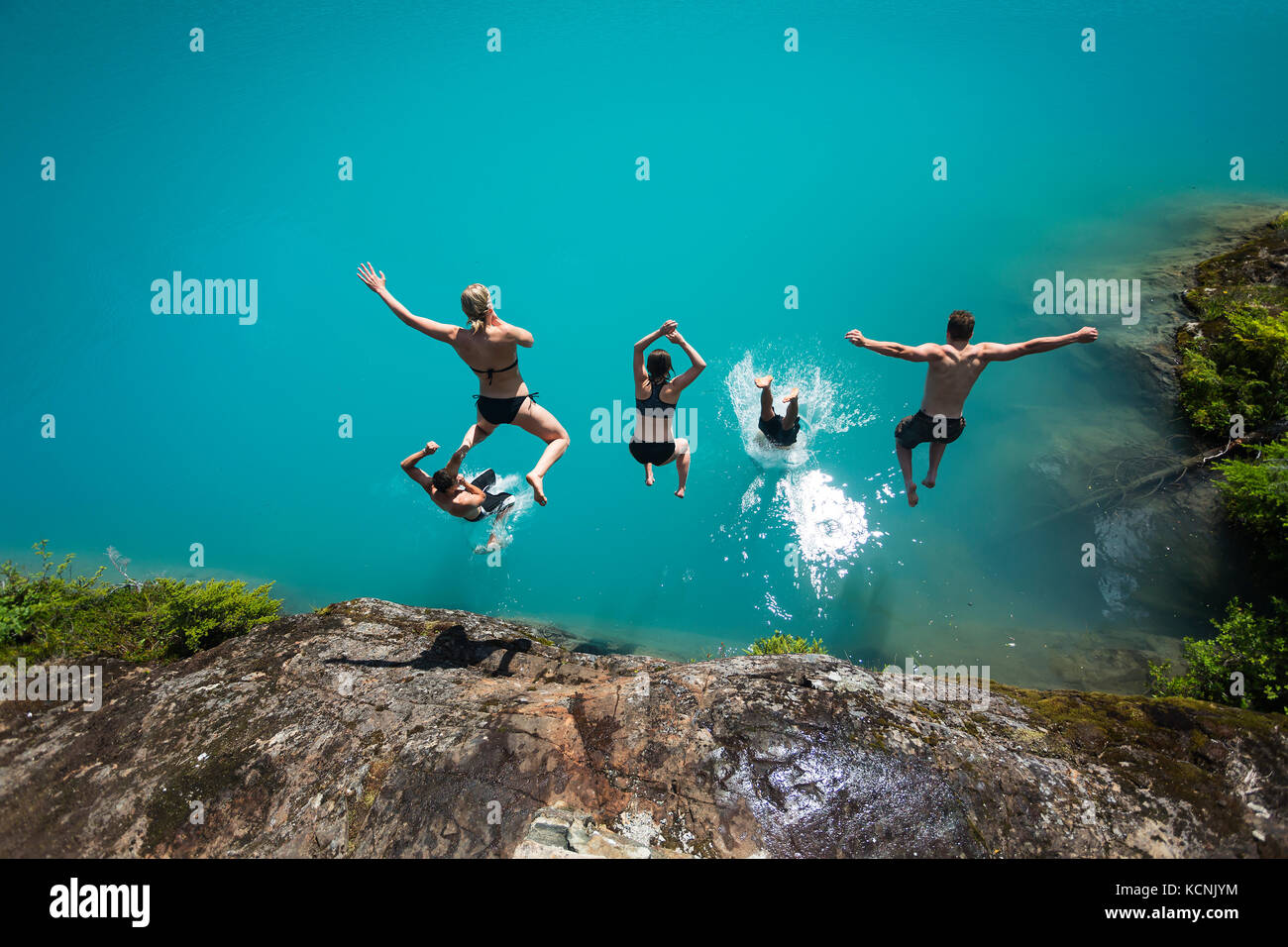 Five friends dive into the turquoise waters of Century Sam lake in Strathcona Park, Vancouver Island, British Columbia, - Stock Image