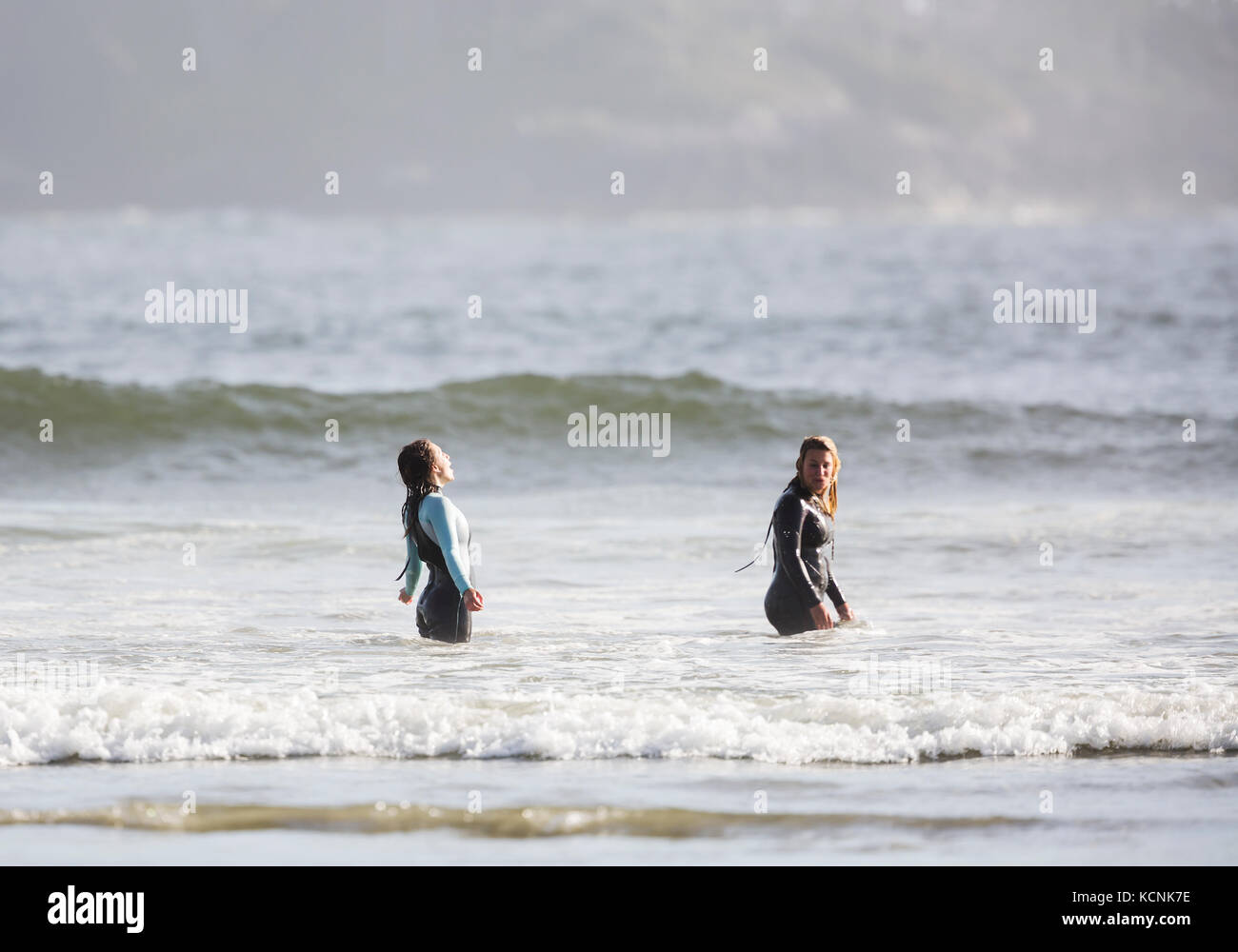 Two friends embrace the moment in the cold waters of Pacific Rim, celebrating a great day of surfing off of Chesterman - Stock Image