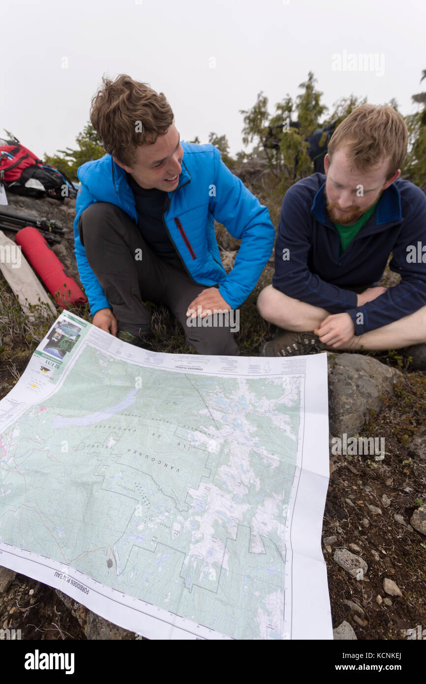 Two friends consult a topographical map while hiking up on Lee Palteau on Vancouver Island, British Columbia, Canada - Stock Image