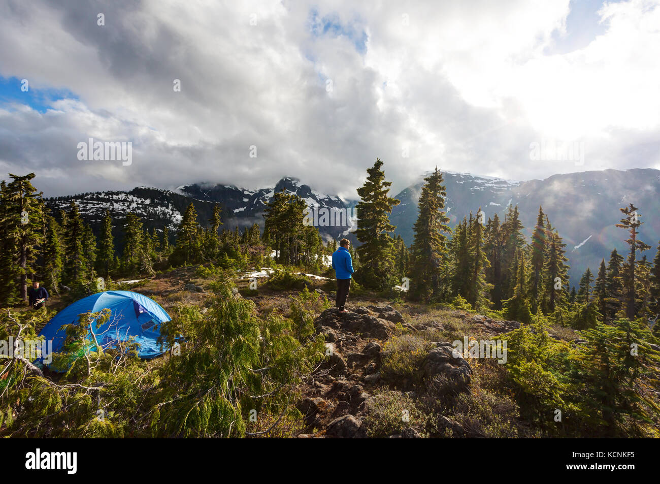 A young hiker looks back onto the Kweishun Canyon while camping on Lee Plateu on Vancouver Island, British Columbia, - Stock Image
