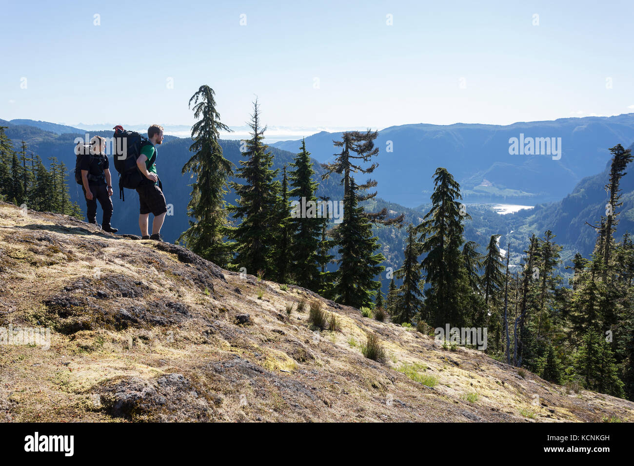 Two hikers stop for a look at the Cruikshank canyon they just climbed enroute to Lee Plateau, Vancouver Island, - Stock Image