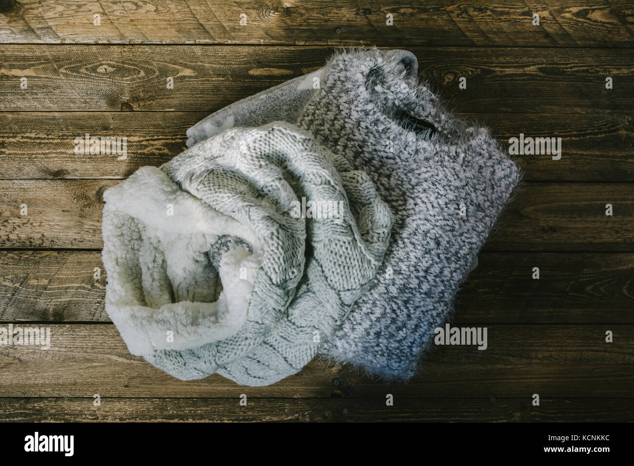 circular wool scarf and gray knit sweater over rustic wood, top view - Stock Image