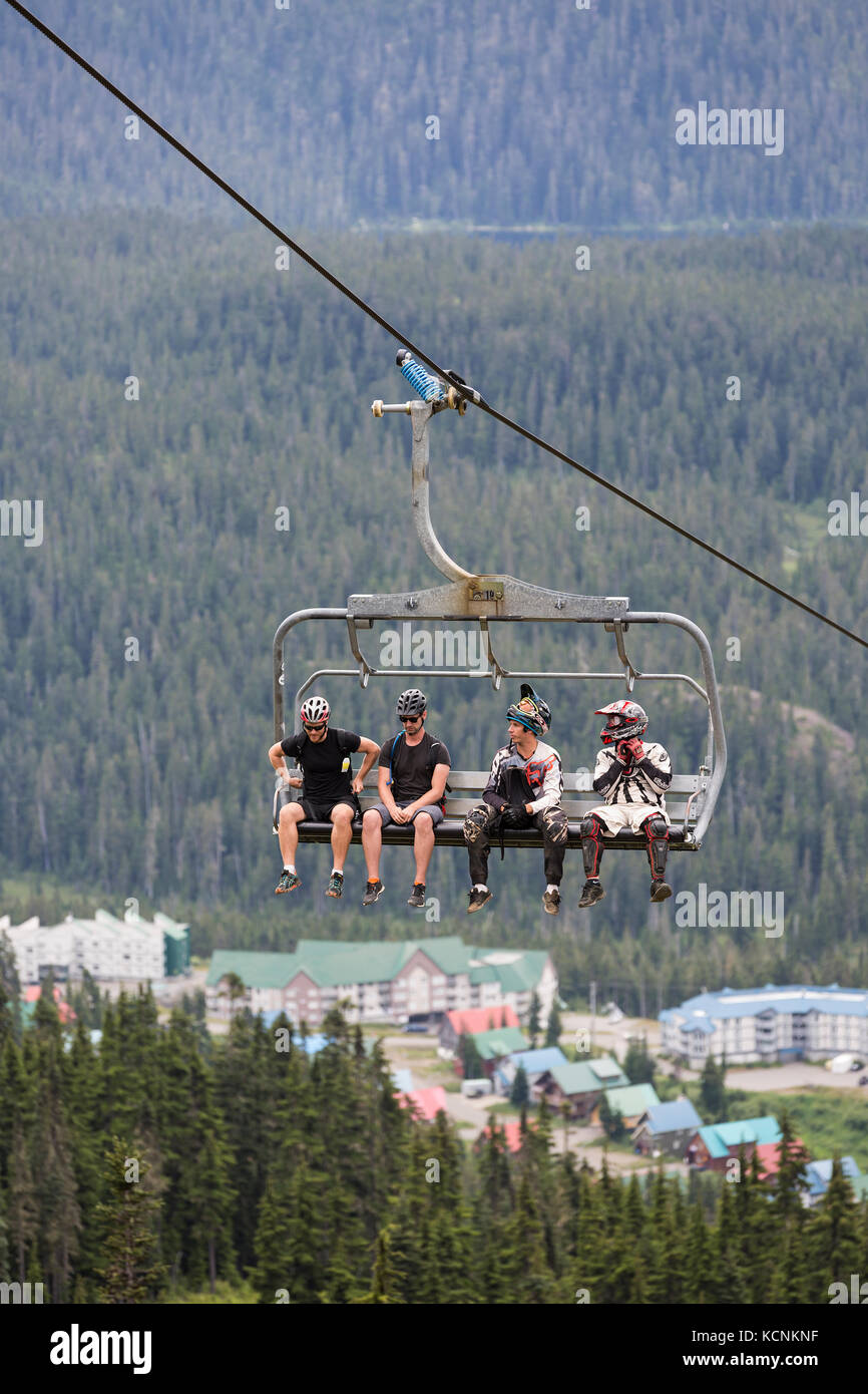 Mountain bikers ride the Hawk chairlift with the village at Mt. Washington in the background. Mt. Washington, The - Stock Image