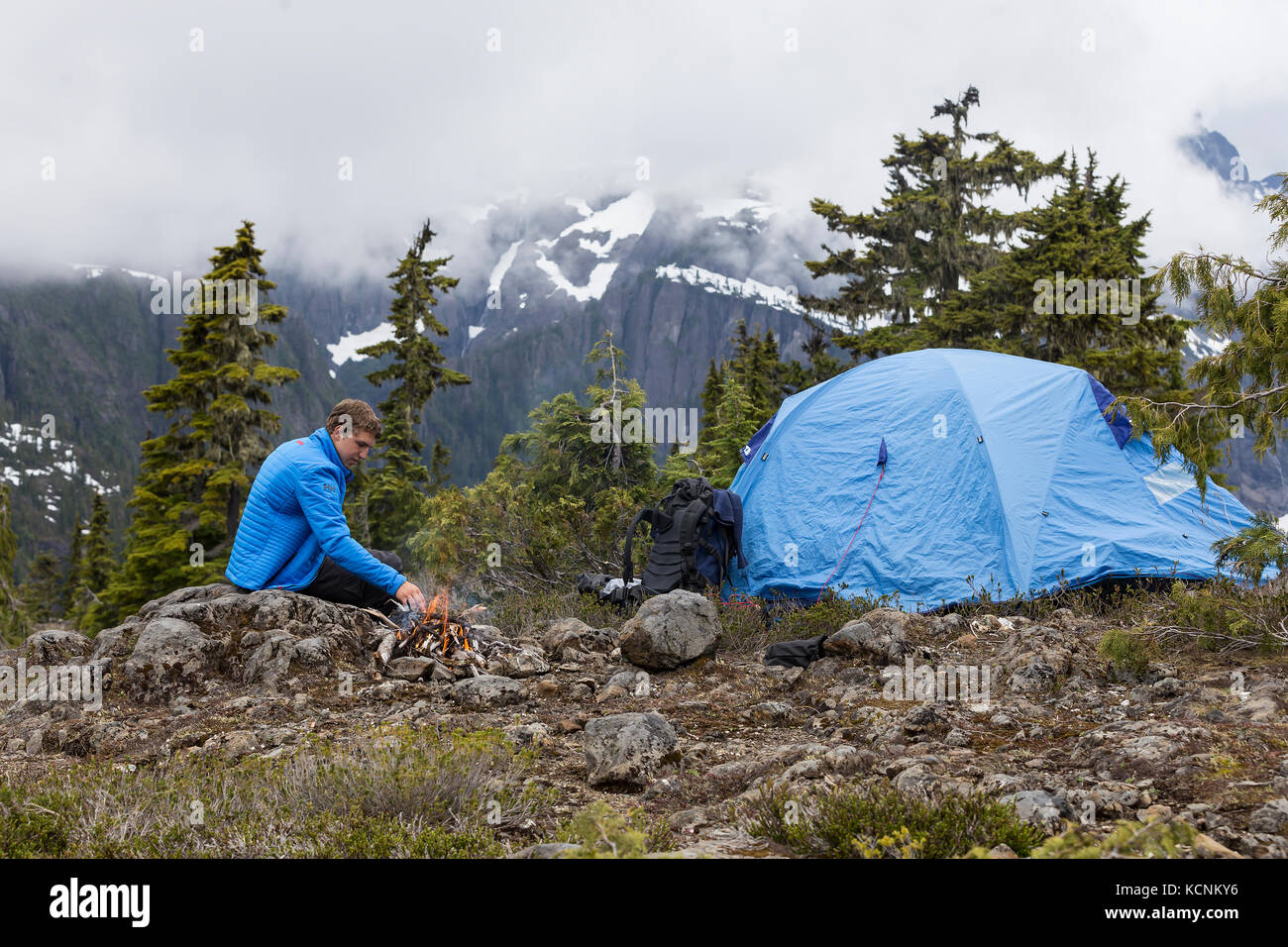 A young hikers tend to a fire while camping on Lee Plateau, Vancouver Island, British Columbia, Canada. - Stock Image