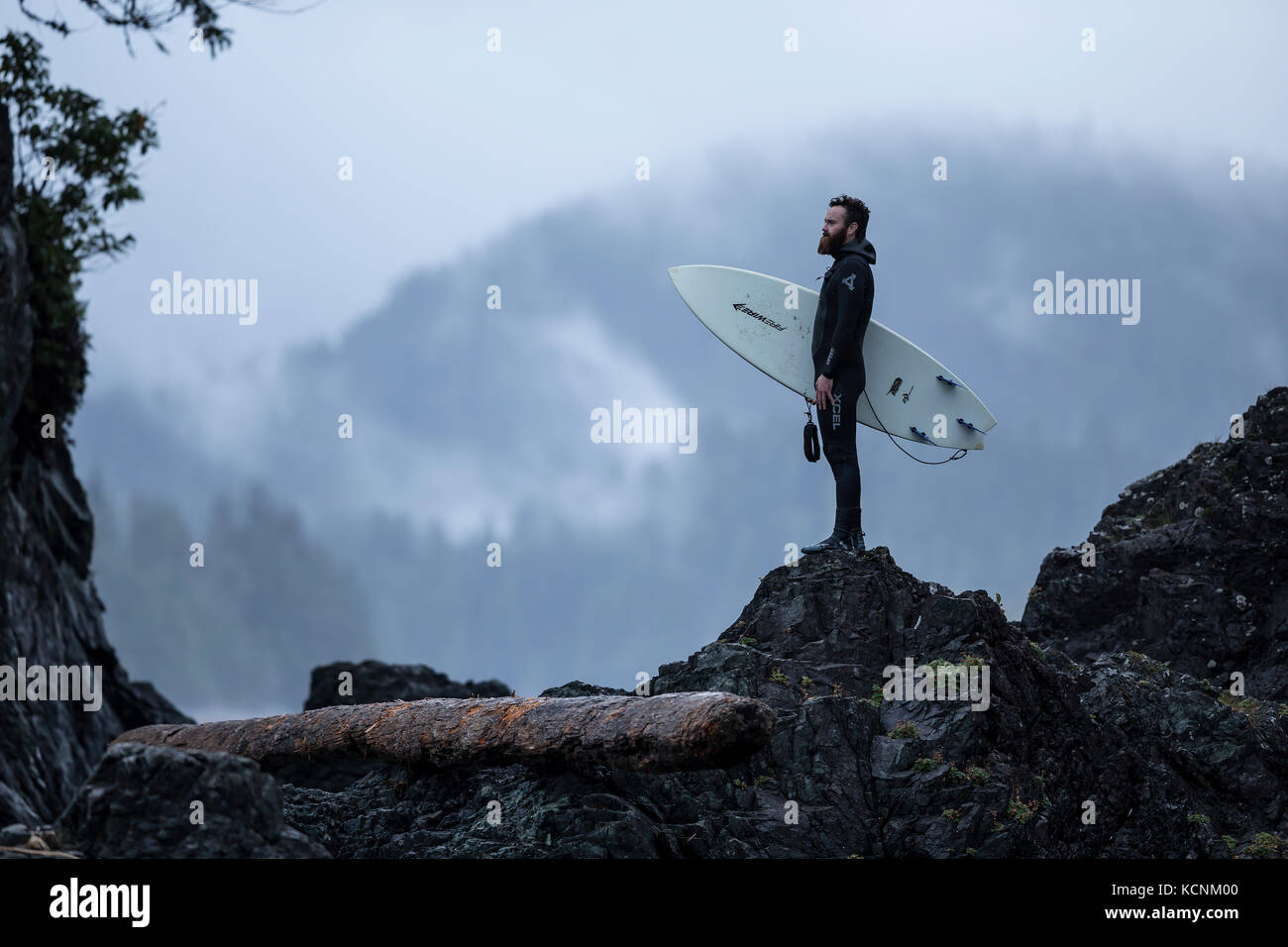 A surfer makes his way back to camp after a recon for waves on Spring Island's westernmost shoreline.  Kyuquot, Vancouver Island, British Columbia, Canada Stock Photo