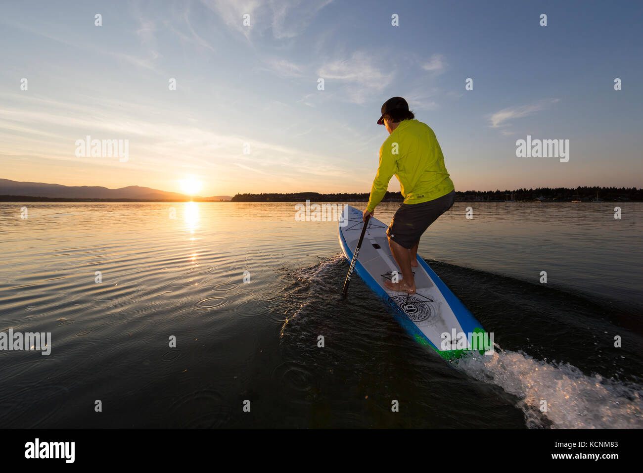 A Stand up paddleboarder launches into the sunset waters off of Goose Spit Regional Park.  Comox, The Comox Valley, - Stock Image