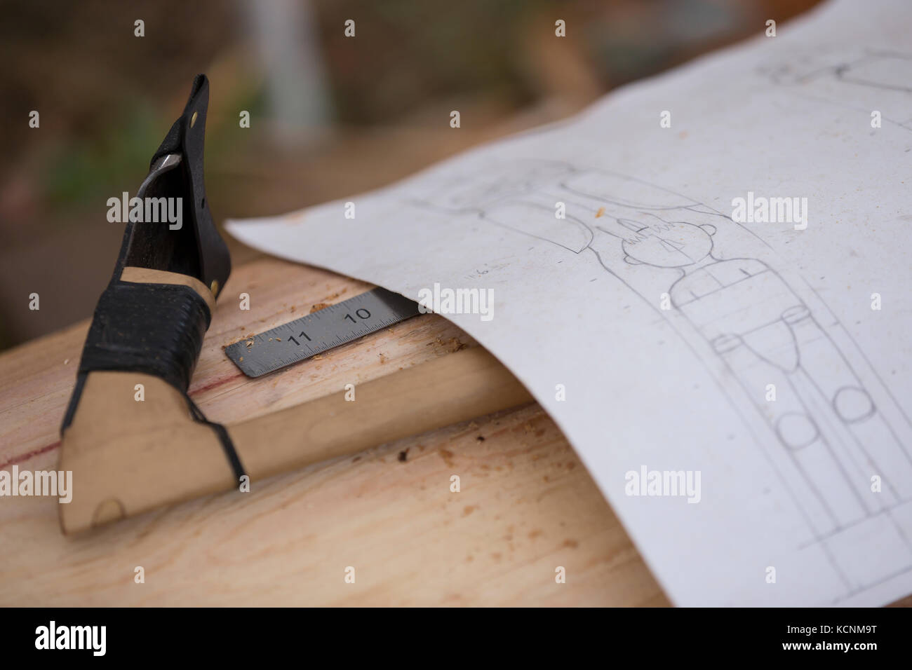 An adze used for roughing out and a drawing of Thunderbird and a man form the beginning of a pole being carved by - Stock Image