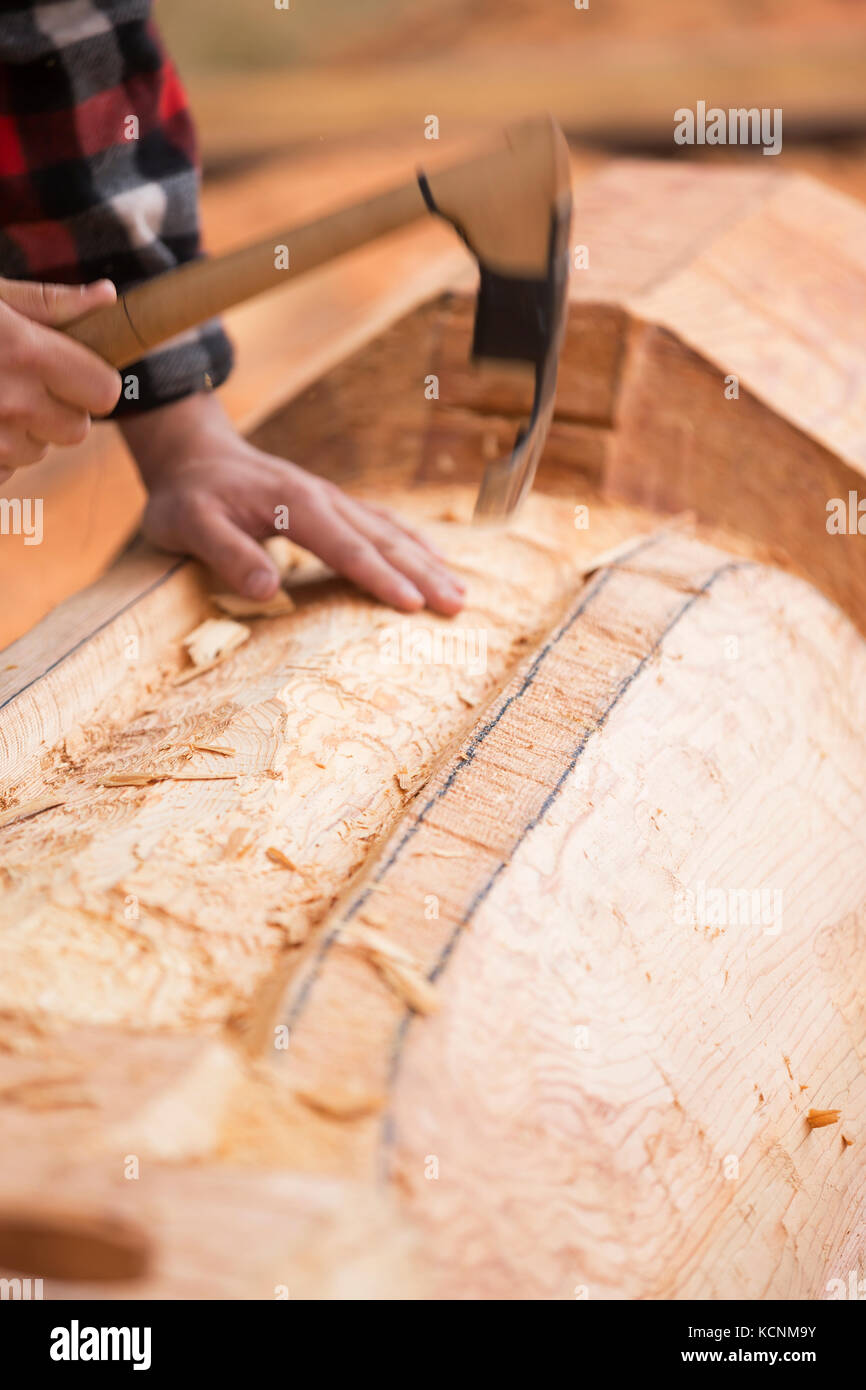 A first nations carver works with an adze roughing out a Thunderbird motif on a pole.  Comox, Vancouver island, - Stock Image