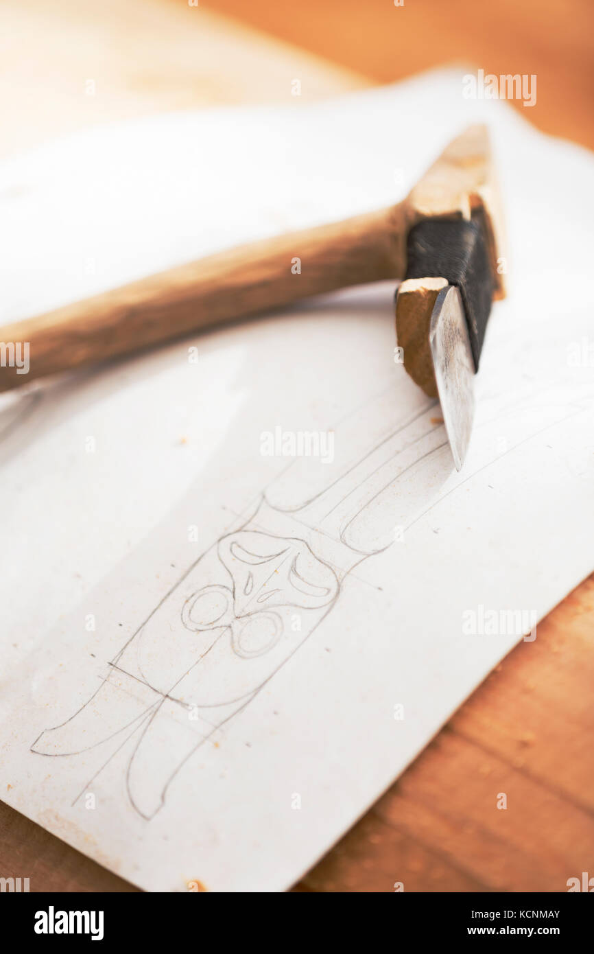 An adze used for roughing out and a drawing of Thunderbird form the beginning of a pole being carved by a local - Stock Image