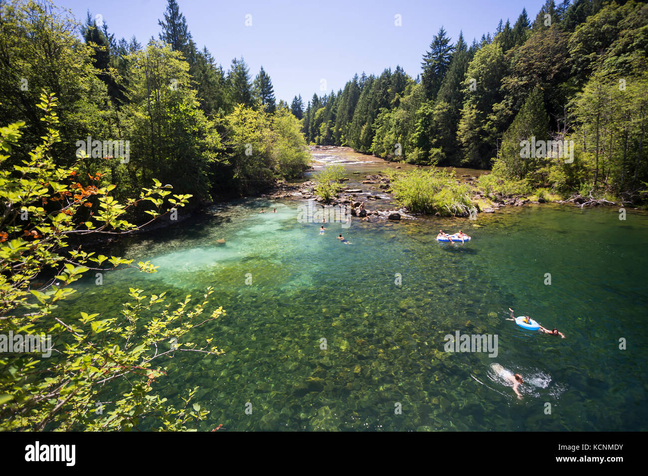 Sun seekers and swimmers migrate to Barbers Hole along the Oyster River, a popular swimming area in the Comox Valley. - Stock Image