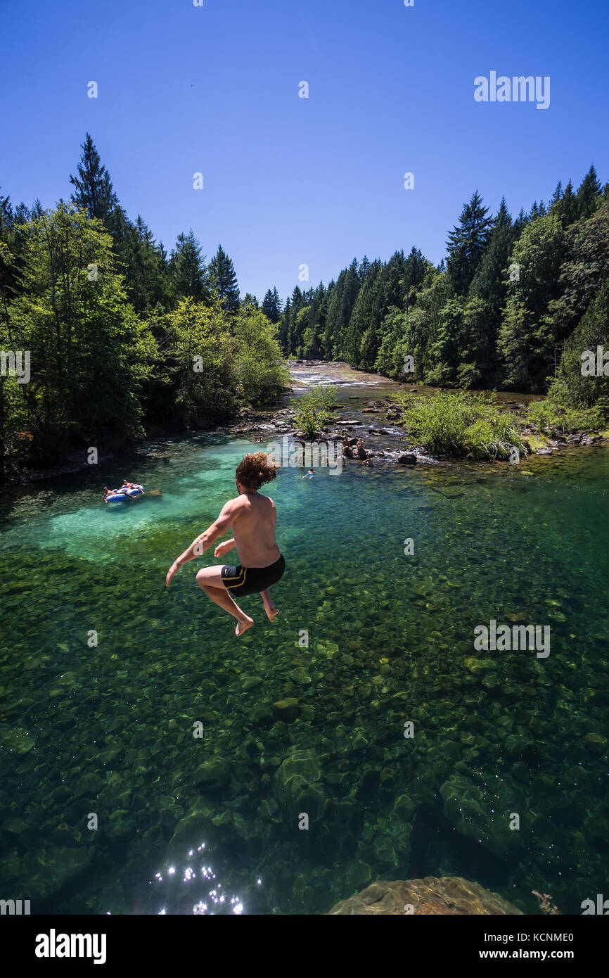 Sun seekers and swimmers migrate to Barbers Hole along the Oyster River, a popular swimming area in the Comox Valley, - Stock Image