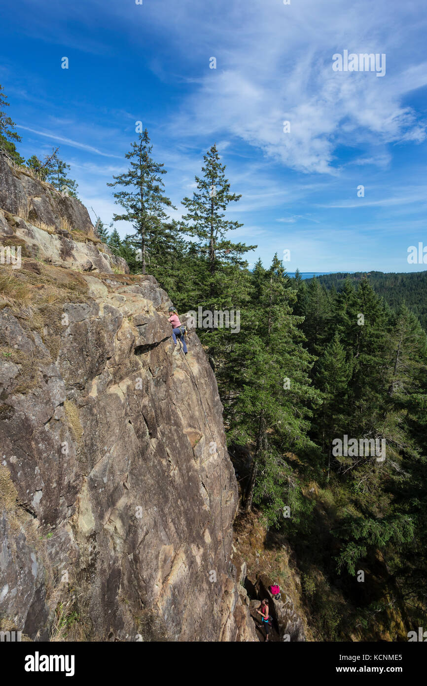 A female rock climber ascends a route on one of the climbing areas near Chinese Mountain.  Quadra Island. Stock Photo