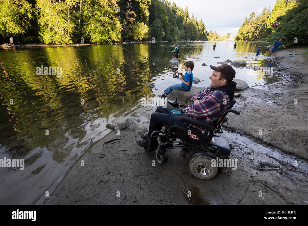 A disabled father and his son fish along the shores of the Campbell River, Vancouver Island - Stock Image