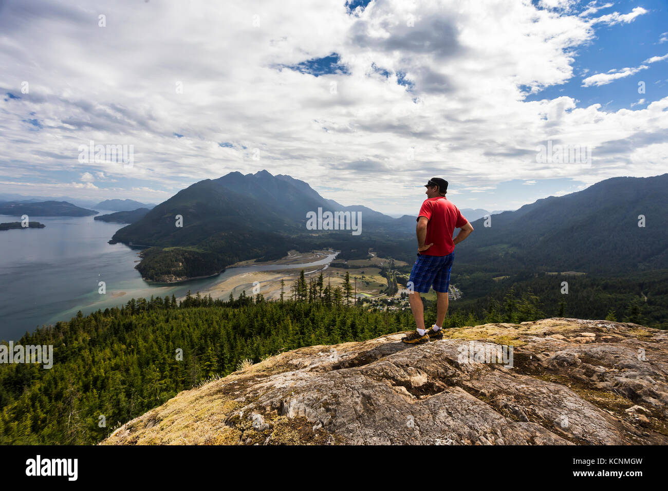 A hiker is rewarded with commanding views of Kelsey Bay, Johnstone strait and the Salmon River Estuary from a viewpoint - Stock Image
