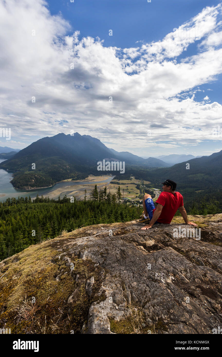 A hiker is rewarded with commanding views of Kelsey Bay and the Salmon River Estuary from a viewpoint high above - Stock Image