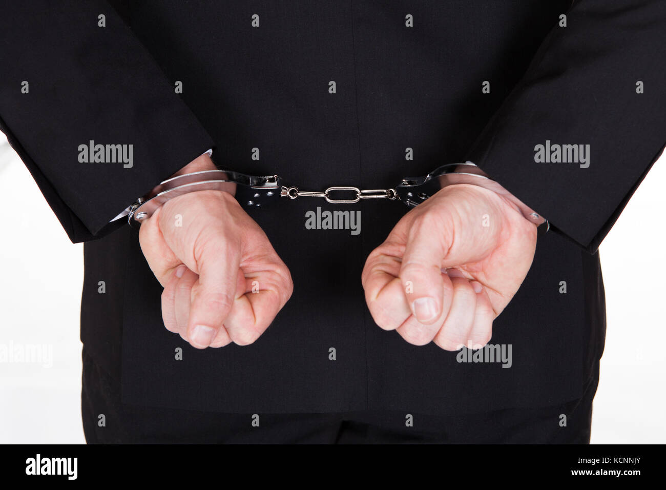 Rear view of arrested businessman with handcuffs - Stock Image