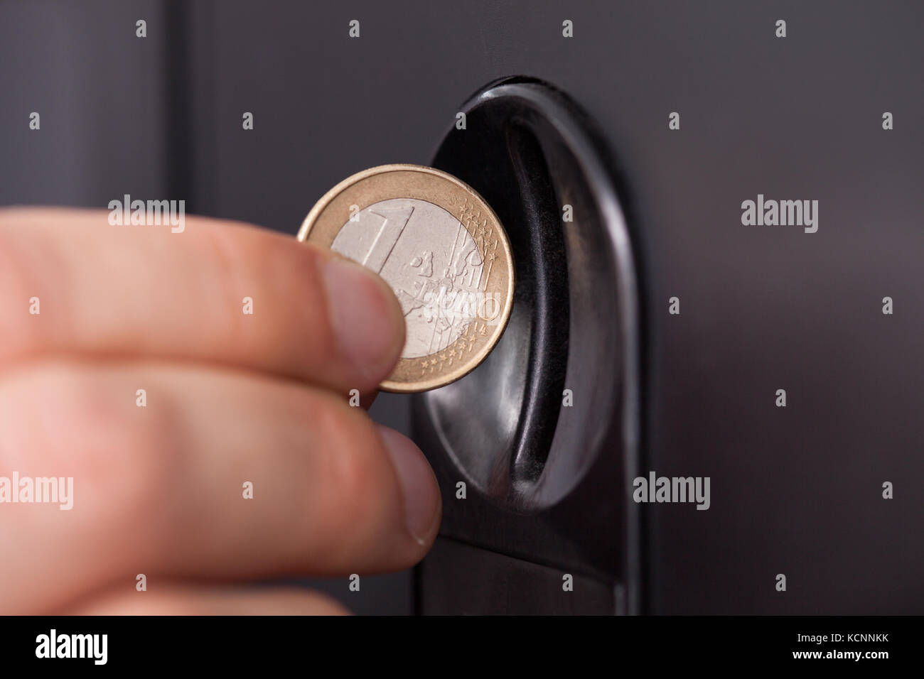 Close-up of human hand inserting coin in vending machine - Stock Image
