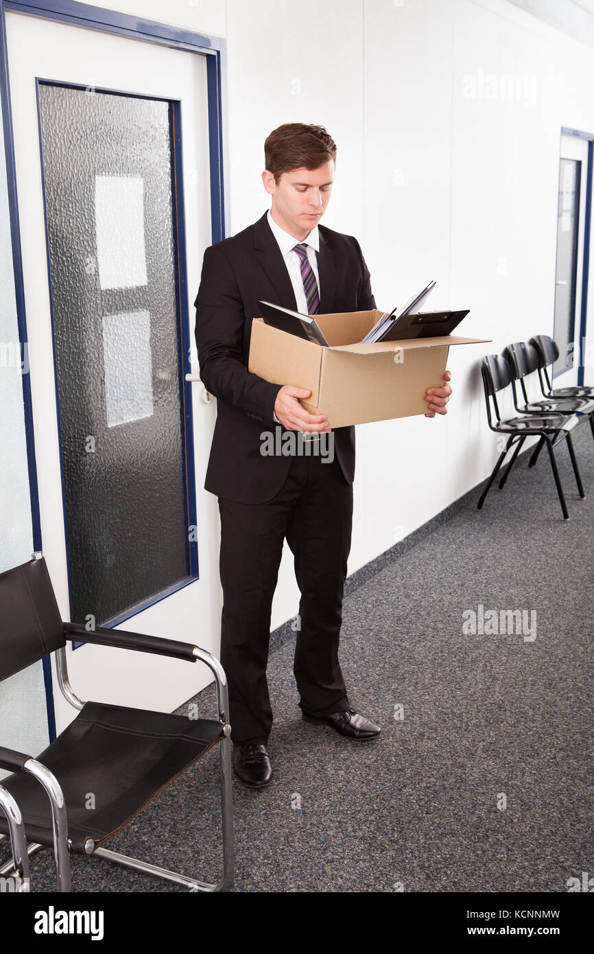 Portrait of young businessman holding cardboard in office - Stock Image