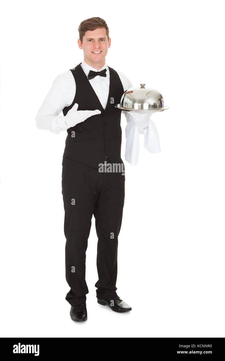 Waiter Holding Empty Silver Tray Over White Background - Stock Image