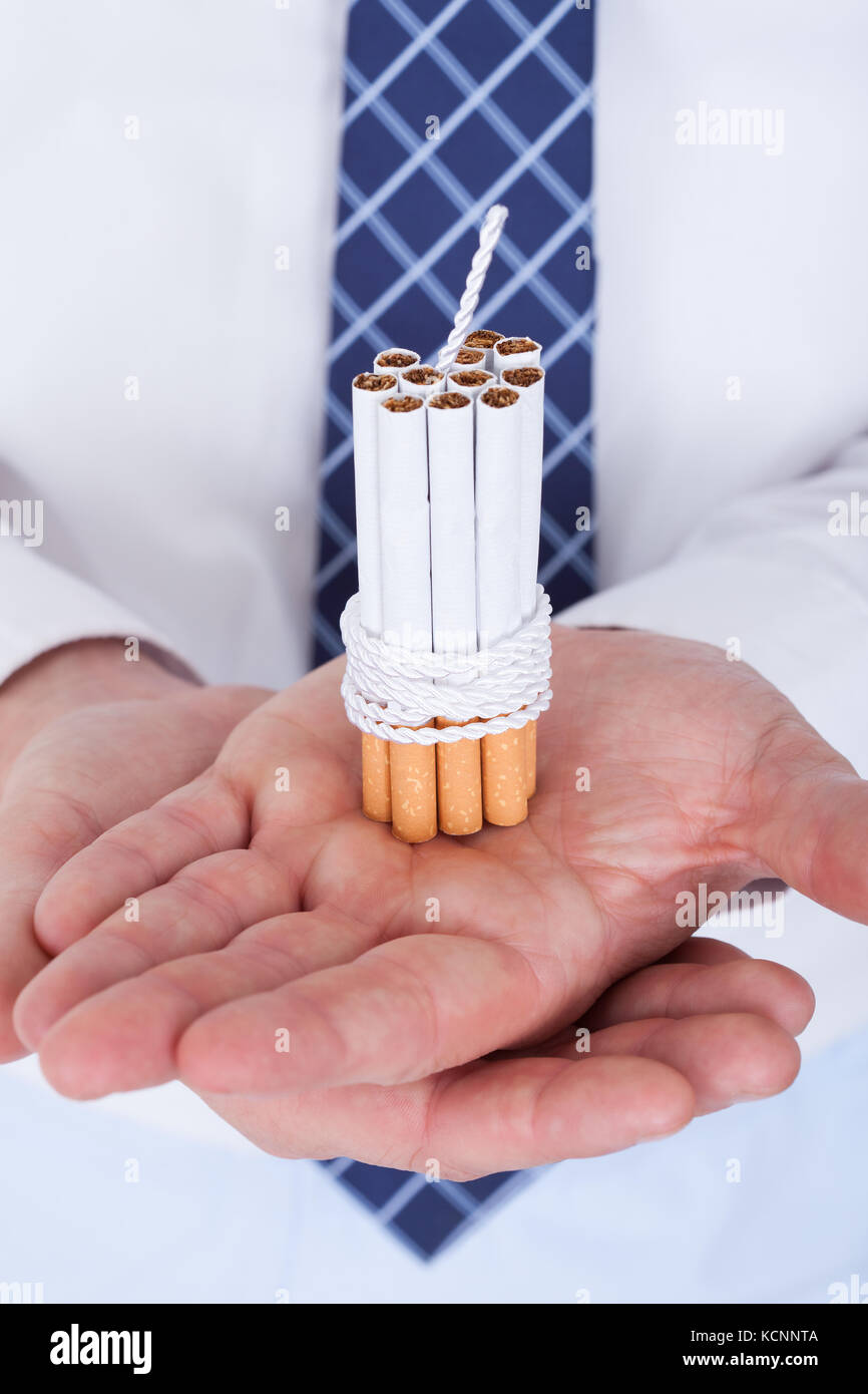 Close-up Of Businessman Holding Cigarettes Tied With Rope And Wick - Stock Image