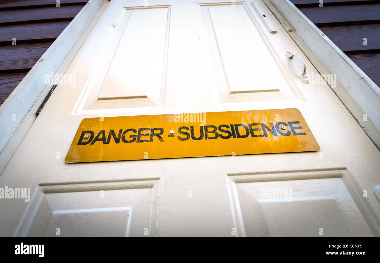 Subsidence warning sign on the front door of a beachside property in Hampshire, UK - Stock Image
