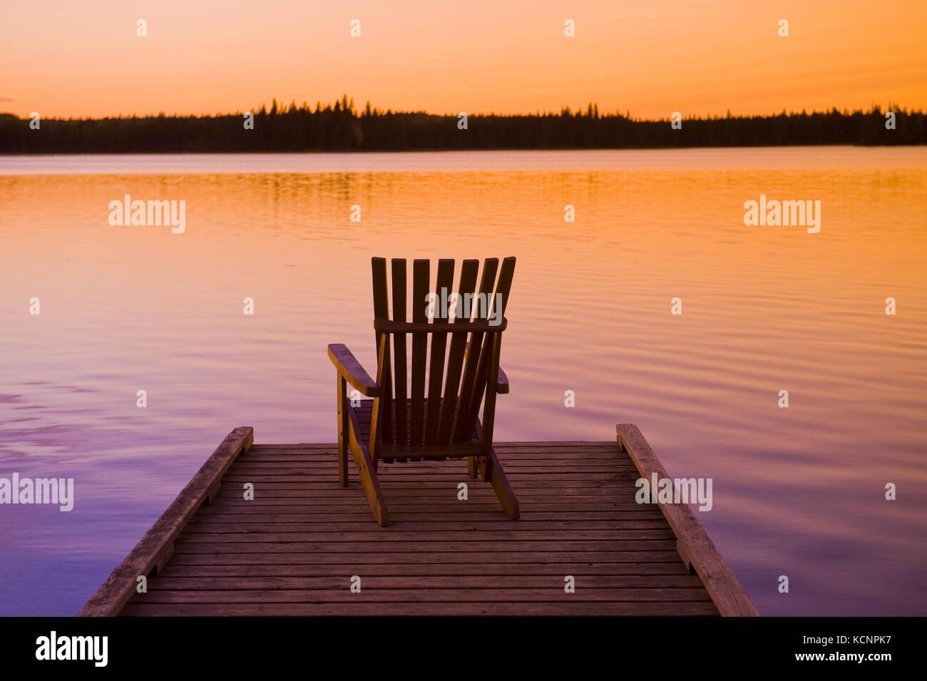 muskoka chair on dock, Beautiful Lake , Duck Mountain Provincial Park, Manitoba, Canada - Stock Image