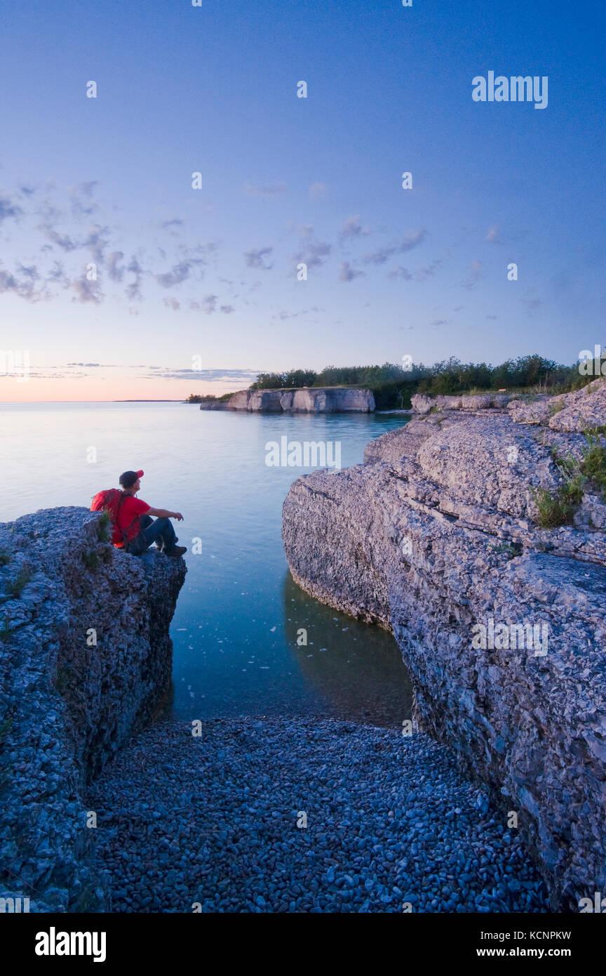 hiker on limestone cliffs, Steep Rock, along Lake Manitoba, Manitoba, ,Canada - Stock Image