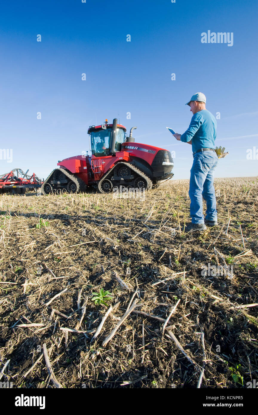 farmer using a tablet in front of a tractor and air seeder, planting winter wheat in a zero till field containing - Stock Image
