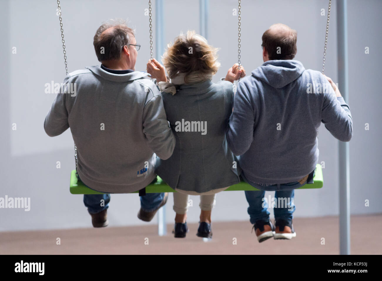 Three people swinging on an exhibit by Danish artists Superflex in the Turbine Hall of the Tate Modern art gallery, - Stock Image