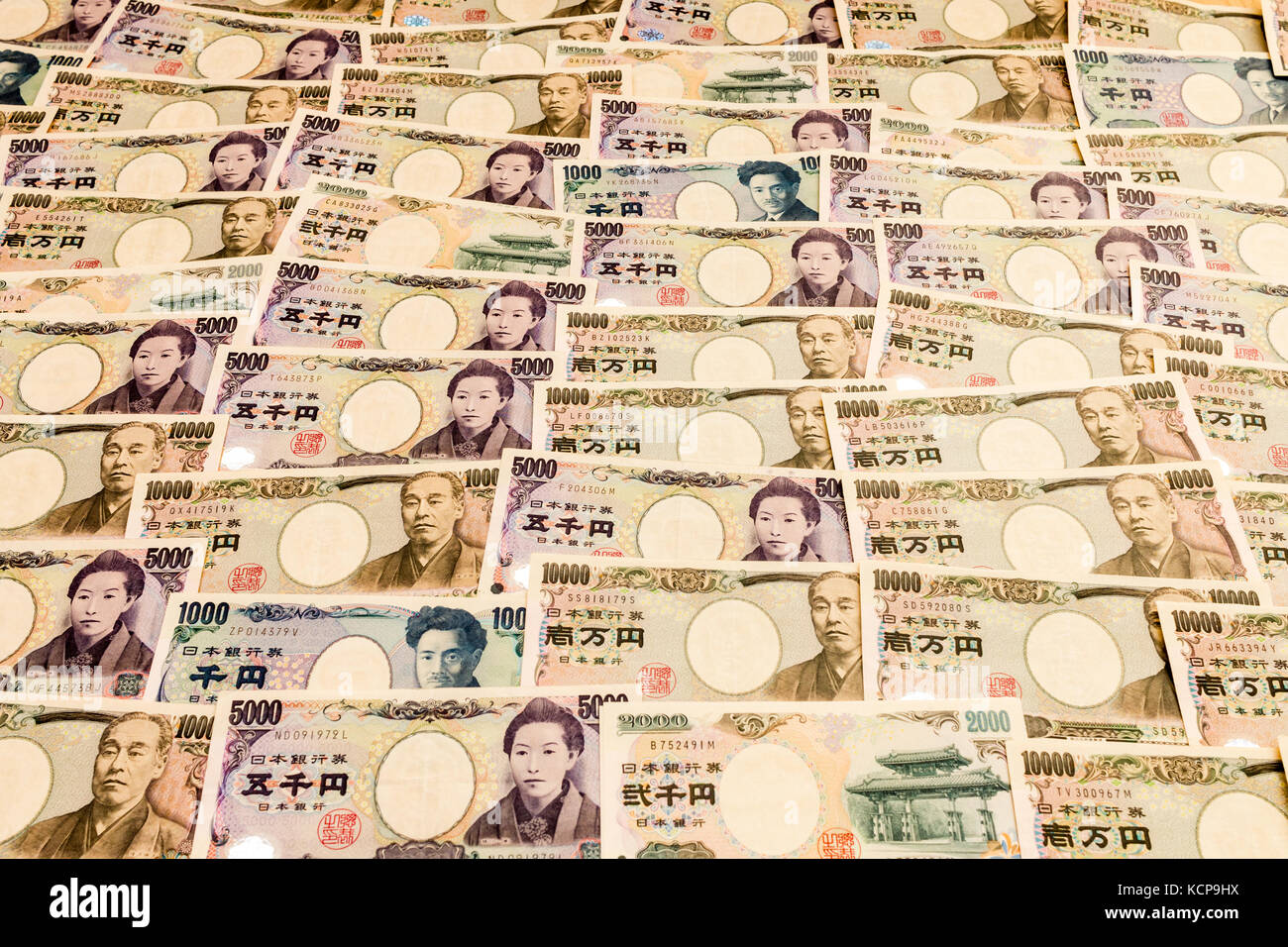 Japanese banknotes of various amounts laid out forming background. - Stock Image