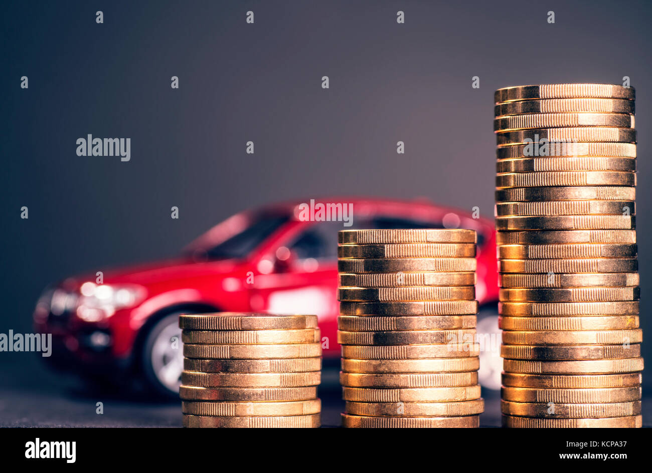 Rising piles of coins and a red car in the background - Stock Image