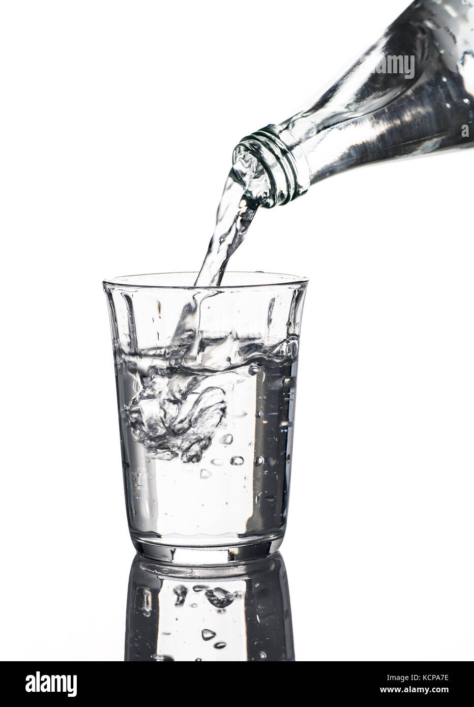 Glass with water and bottle in front of a white background - Stock Image