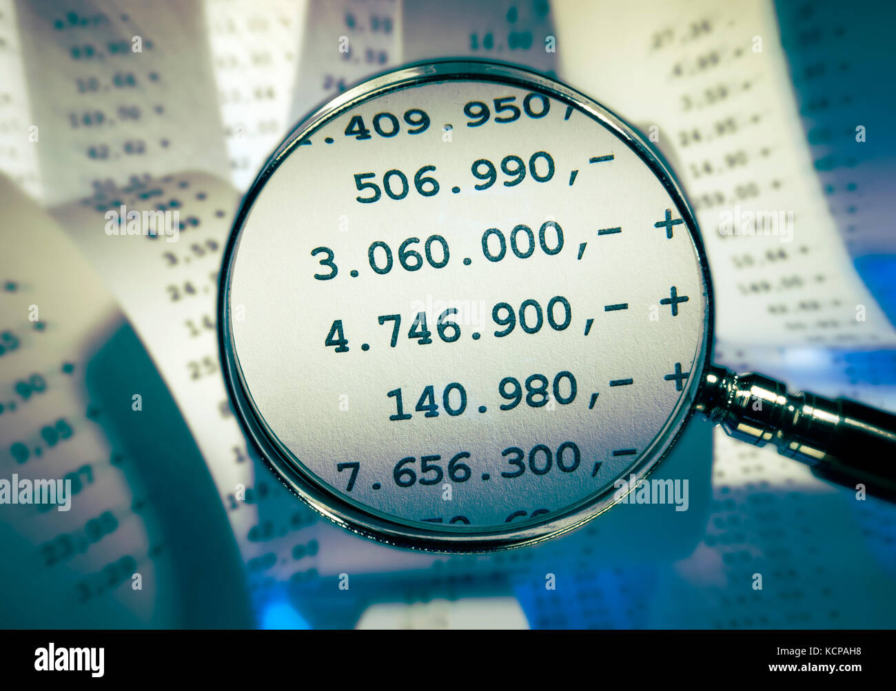 Magnifier focussing high sums in front of a background with receipts - Stock Image