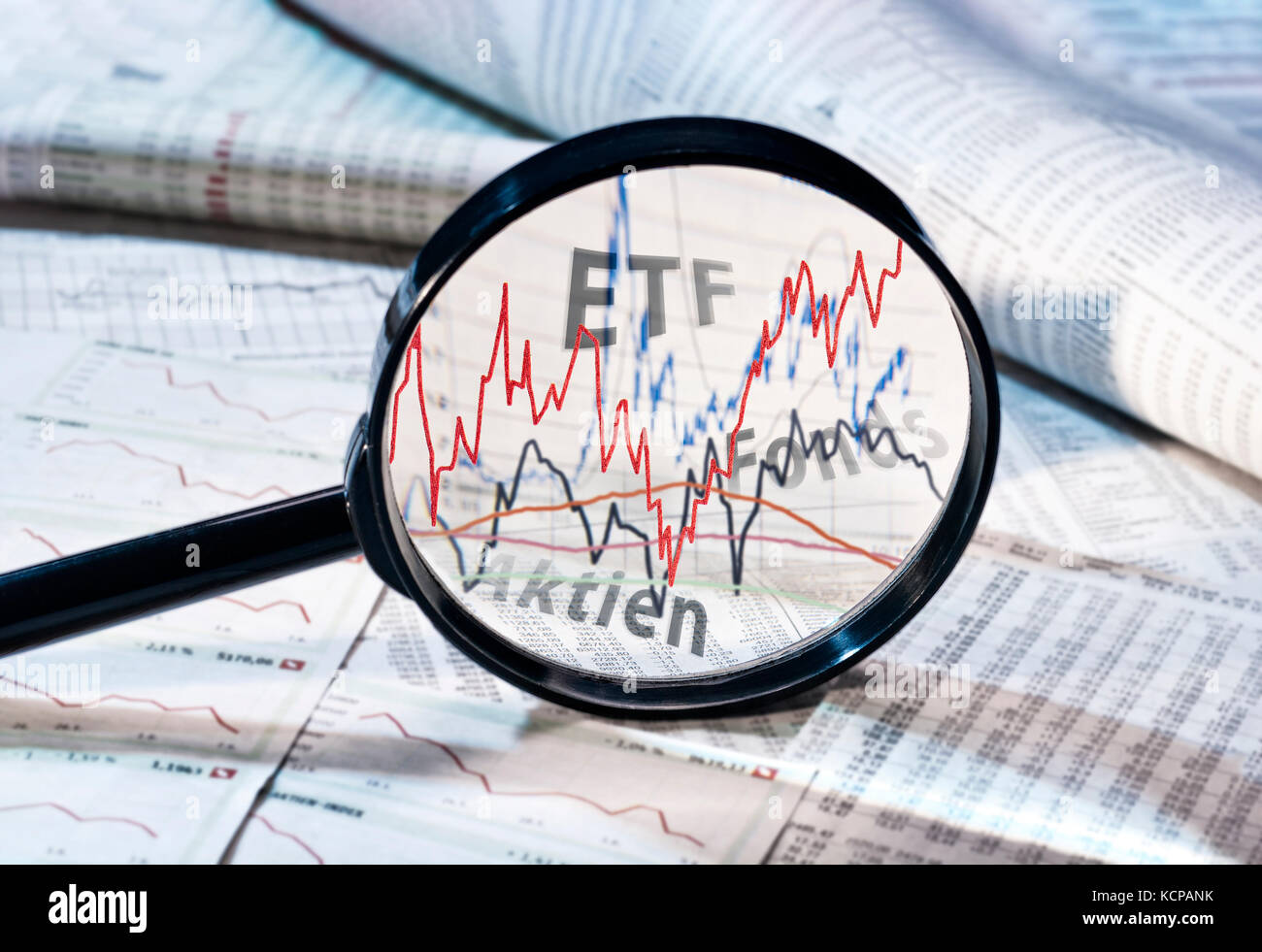 Magnifying glass shows the courses of ETF, funds and shares Stock Photo