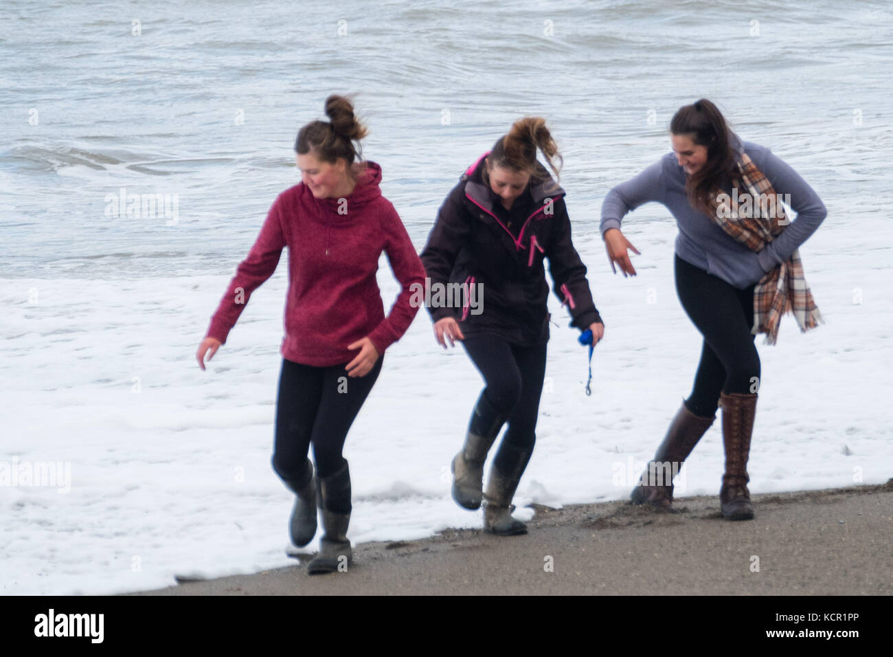 144154f6 Aberystwyth Wales UK, Saturday 07 October 2017 UK Weather: ~Three young  women get caught by the waves as they walk along the beach on a cloudy and  breezy ...