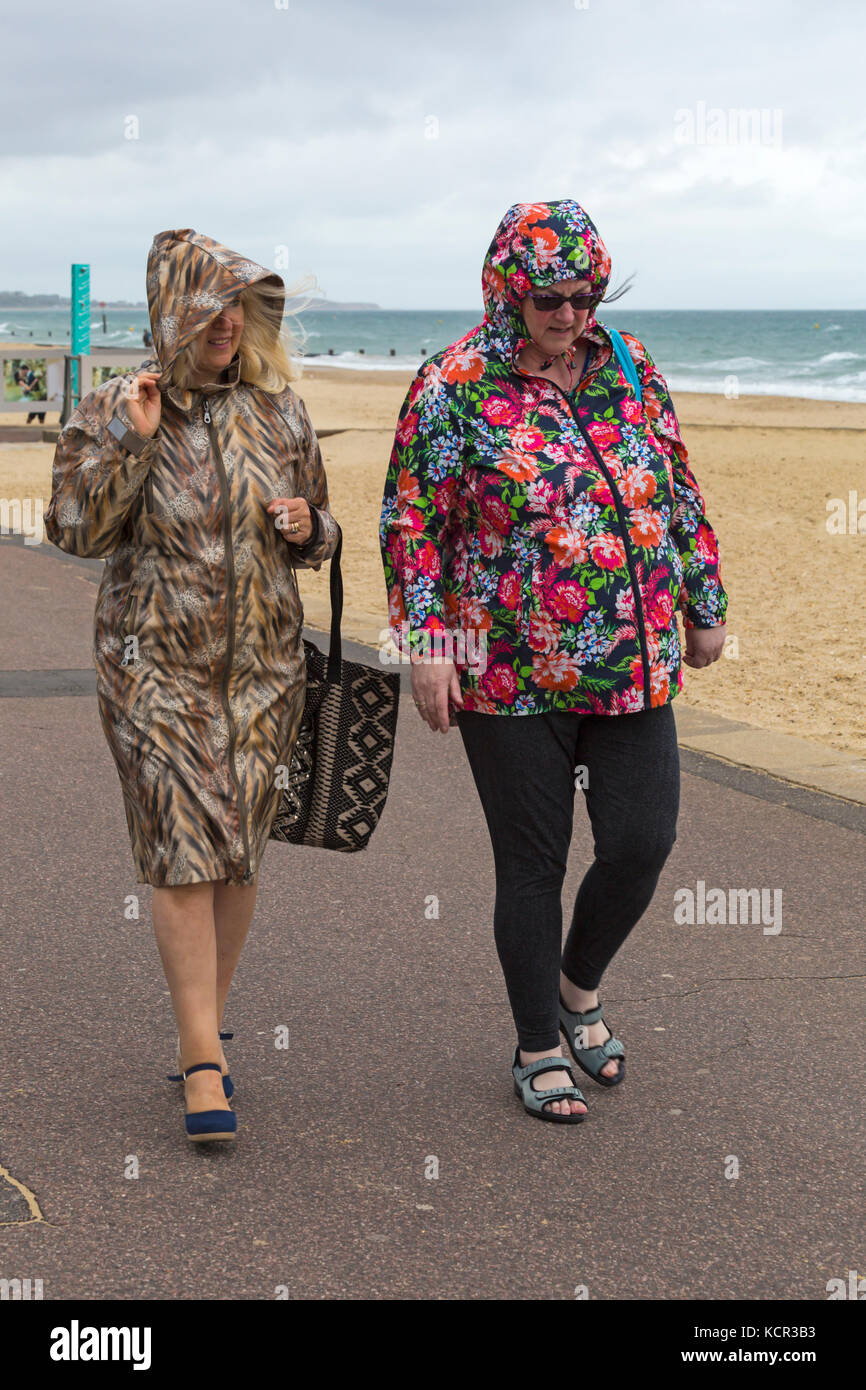 65e6fb04 UK weather: breezy and overcast at Bournemouth beach with some drizzle, as  two women walk along the promenade seafront in colourful coats with hoods  up.