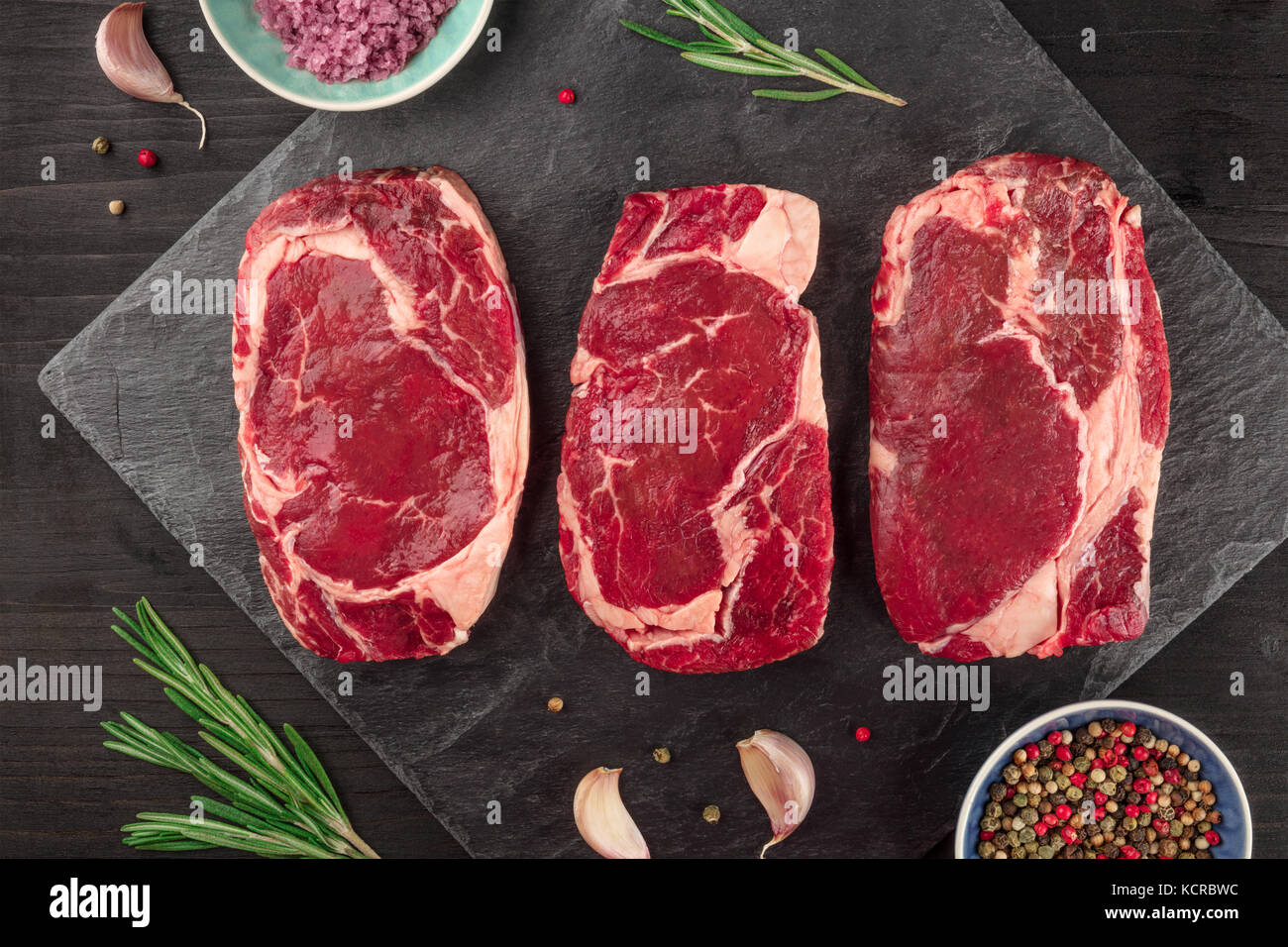 A closeup of three slices of raw meat, beef fillet, shot from above on black textures with sprigs of rosemary, salt, - Stock Image