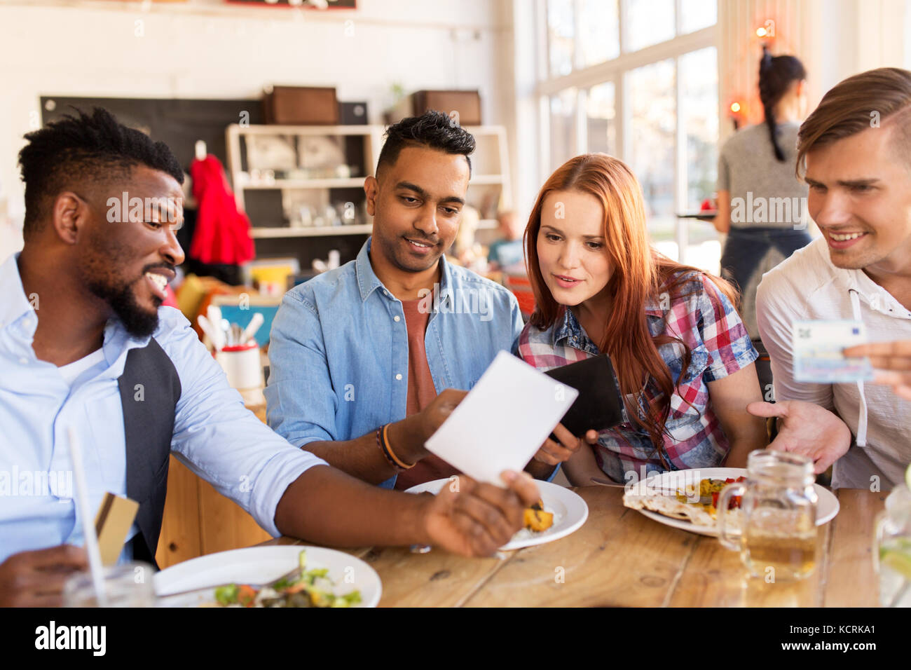 Happy Friends With Money Paying Bill At Restaurant Stock