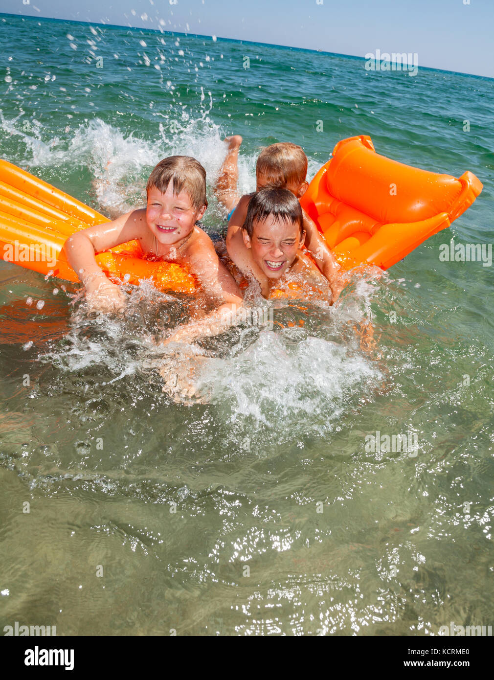 Three kids having fun floating on a inflatable mattress in the sea - Stock Image