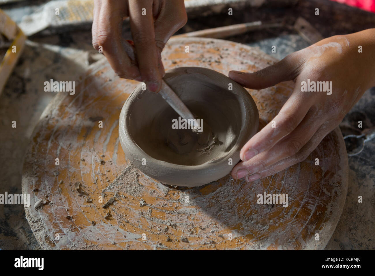 Hands of female potter molding a bowl with hand tool in potter workshop - Stock Image