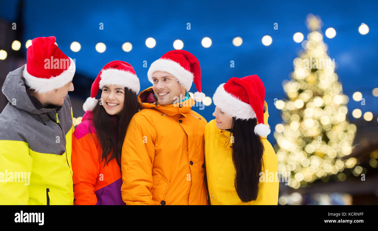 friends in santa hats and ski suits at christmas - Stock Image