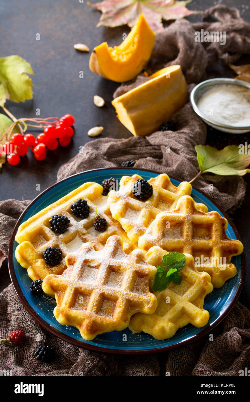 Breakfast table with pumpkin waffles, milk and fresh blackberry berries on a wooden kitchen table. - Stock Image